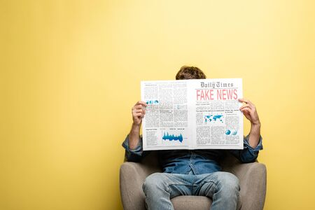 young man sitting in armchair and reading newspaper with fake news on yellow background