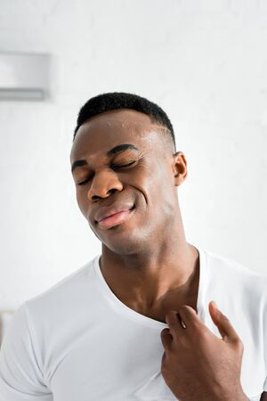 exhausted african american man closing eyes and standing in room with heat temperature
