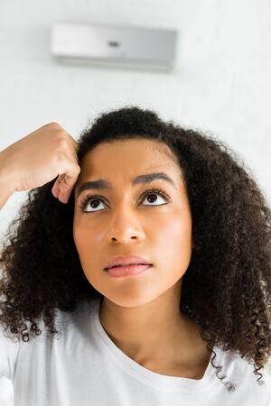 portrait of upset african american woman looking away and standing in room with air condition