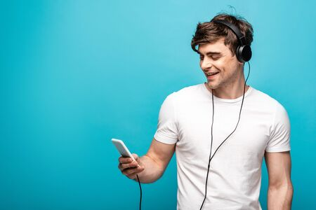 handsome young man smiling while listening music with headphones and smartphone on blue background
