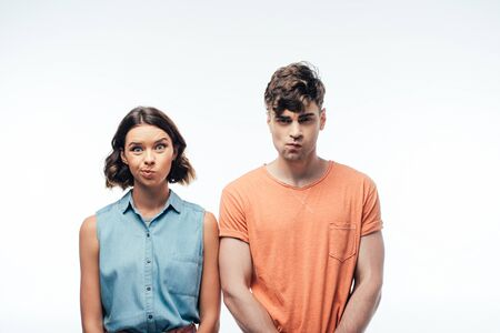 young, displeased man and woman looking at camera and grimacing on white background