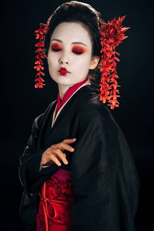 beautiful geisha in black and red kimono and flowers in hair looking down isolated on black