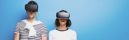 panoramic shot of young man and woman using virtual reality headsets on blue background
