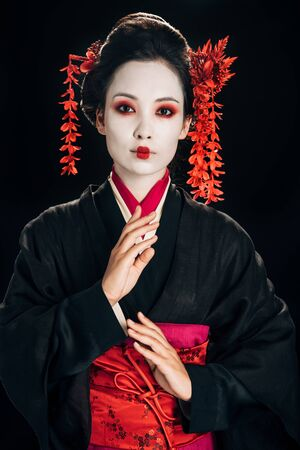beautiful geisha in black and red kimono gesturing isolated on black