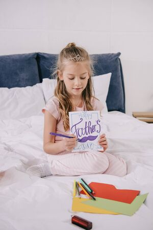 adorable child drawing fathers day greeting card while sitting on bedding