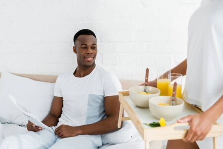 happy african american man lying on white bed, and looking on tray in girlfriend hands