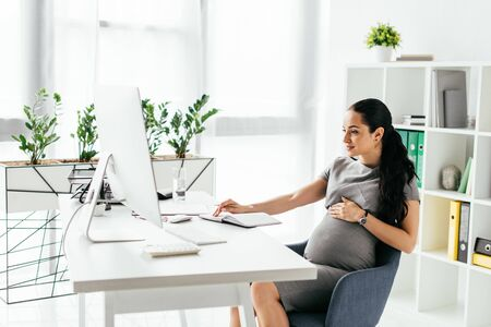 pregnant woman sitting in room with bookcase and flowerpot with plants behind table and working on computer