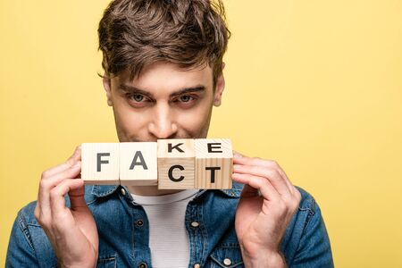 positive young man looking at camera while showing wooden cubes with fake fact lettering  on yellow background Stock Photo
