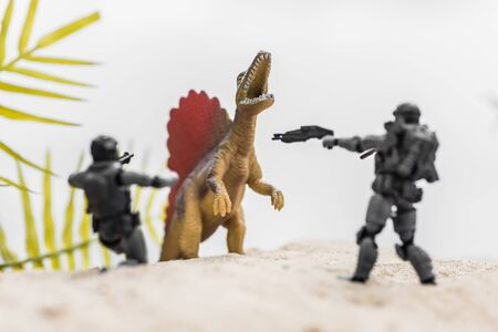 selective focus of toy soldiers aiming guns on roaring tiny dinosaur on sand hill