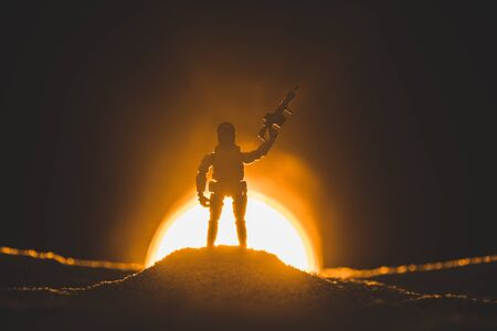 silhouette of toy soldier with gun and sun on background
