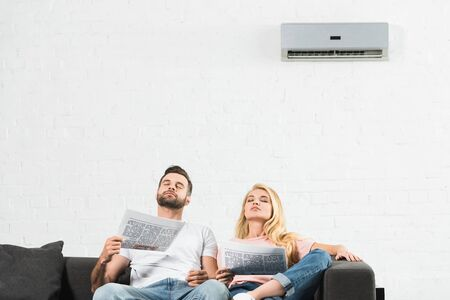 couple on couch with newspapers suffering from heat under air conditioner at home