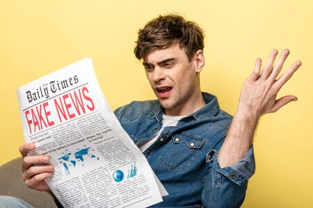 displeased young man sitting in armchair and reading fake news on yellow background Stockfoto
