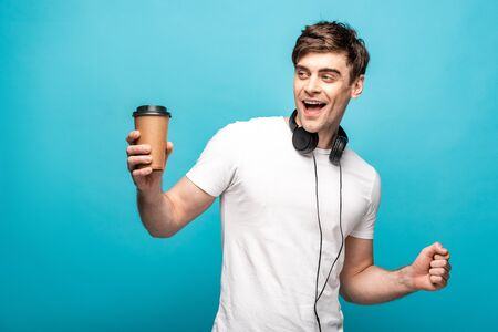 cheerful man with headphones looking away while holding paper cup on blue background 版權商用圖片