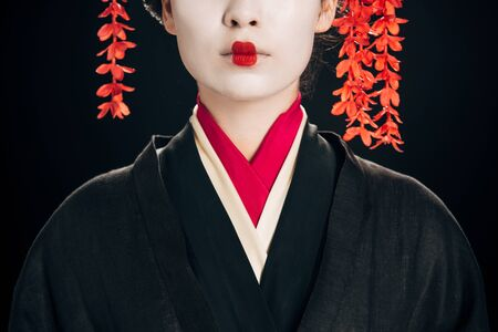 partial view of beautiful geisha in black and red kimono isolated on black