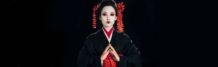 beautiful geisha in black and red kimono and flowers in hair with clenched hands isolated on black, panoramic shot