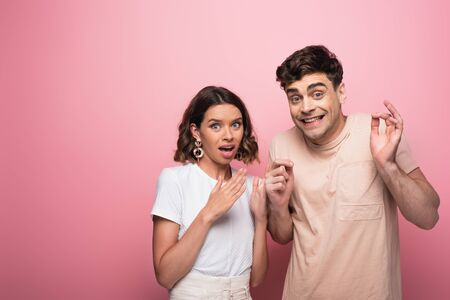 emotional man and woman gesturing shut up while looking at camera on pink background