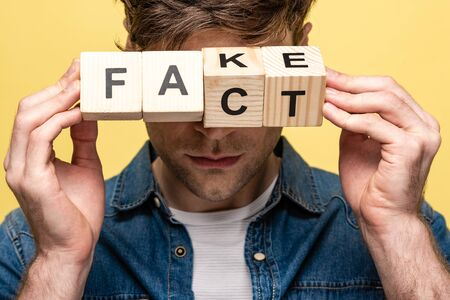 cropped view of man holding wooden cubes with fake fact lettering isolated on yellow