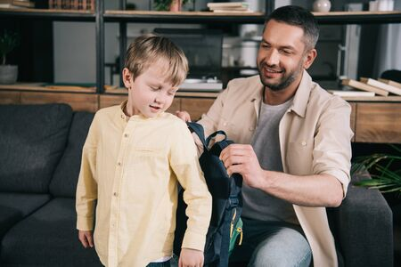 smiling dad helping cute boy putting on backpack at home