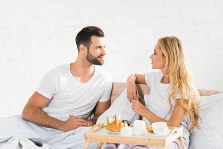 beautiful couple in pajamas having breakfast in bed in morning Standard-Bild - 128084285