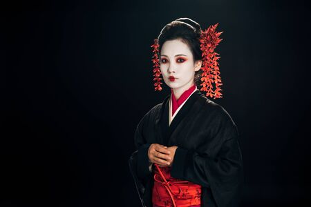 calm beautiful geisha in black and red kimono and flowers in hair isolated on black 版權商用圖片