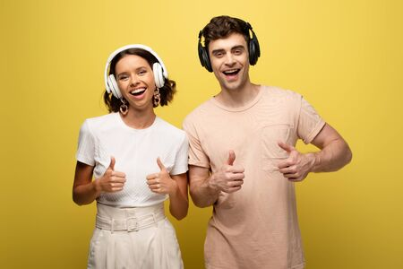 cheerful man and woman showing thumbs up while smiling at camera on yellow background