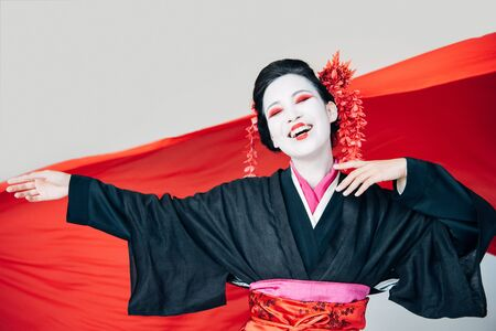 happy beautiful geisha in black kimono with red cloth on background isolated on white