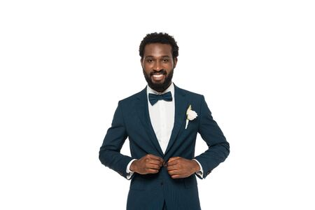 cheerful bearded african american man touching suit isolated on white