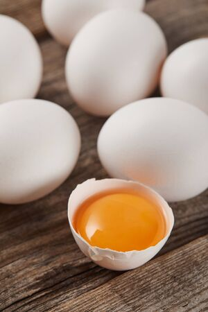 selective focus of broken eggshell with yellow yolk near eggs on wooden table