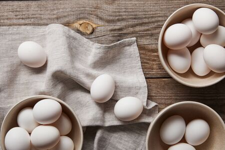 top view of chicken eggs in bowls on wooden table with cloth