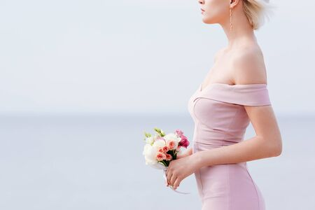 cropped view of slim elegant woman holding wedding bouquet