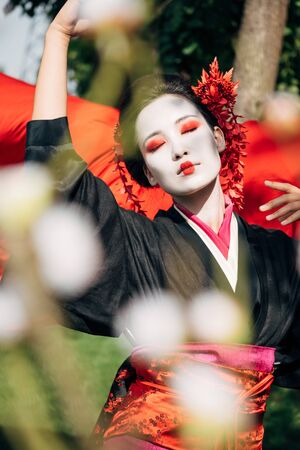 selective focus of tree branches and beautiful dancing geisha with red cloth on background in sunlight Stock Photo