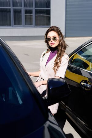 selective focus of serious young woman in sunglasses standing near cars Stock Photo