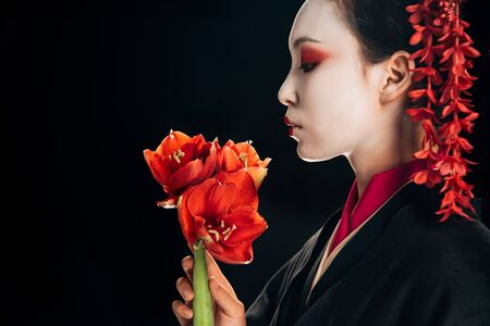 side view of beautiful geisha in black kimono with red flowers isolated on black