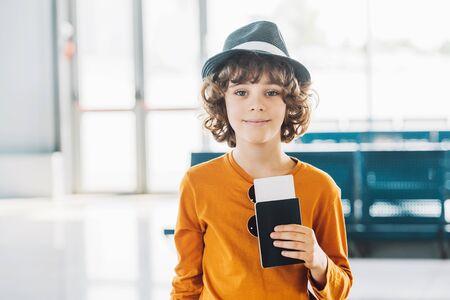 preteen chłopiec z paszportem i biletem lotniczym na lotnisku patrząc na kamerę