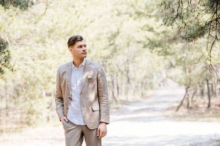 pensive bridegroom in formal wear standing with hand in pocket and looking away