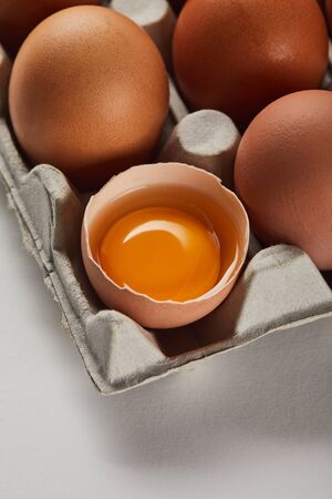 broken eggshell with yellow yolk near eggs in carton box Banco de Imagens - 128093390