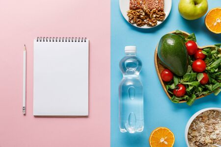 top view of bottle with water and diet food near blank notebook on blue and pink background