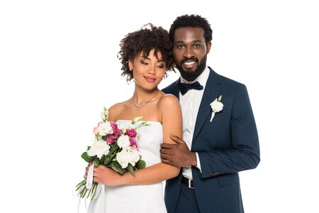 happy african american bride holding flowers near handsome bridegroom looking at camera isolated on white