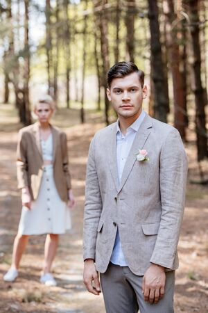 stylish groom with boutonniere on jacket and bridegroom standing in forest and looking at camera