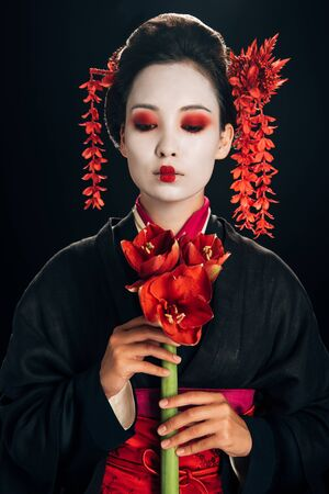 young geisha in black kimono with red flowers isolated on black