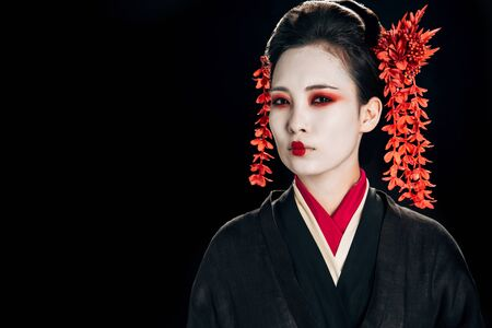 serious geisha in black and red kimono and flowers in hair isolated on black
