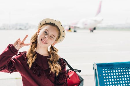 cute preteen kid sticking out tongue and showing Peace Sign in airport