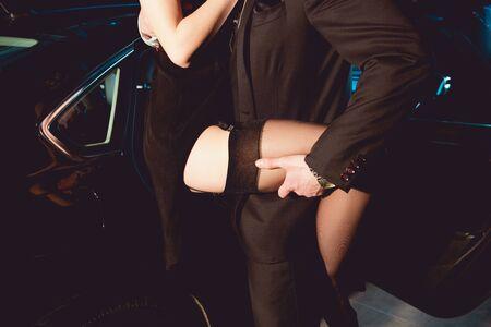 Vista recortada del elegante hombre abrazando a chica en medias cerca del coche