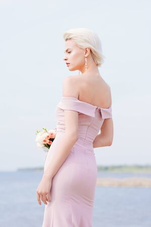 pensive blonde girl in pink dress holding bouquet Stok Fotoğraf