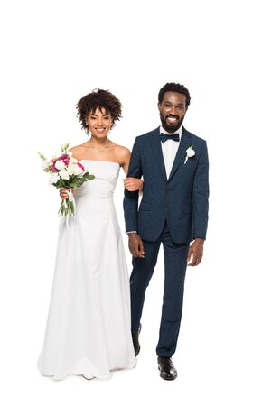 happy african american bride holding flowers near bearded bridegroom isolated on white