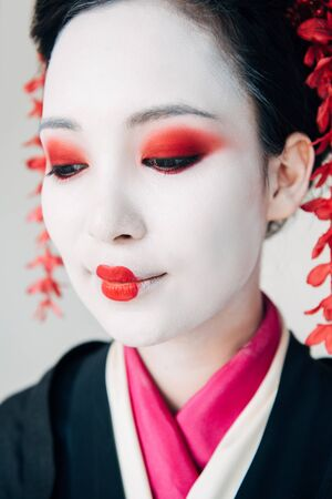 close up view of smiling beautiful geisha in black kimono with red flowers in hair isolated on white