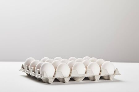 chicken eggs in carton box on white surface Stock Photo