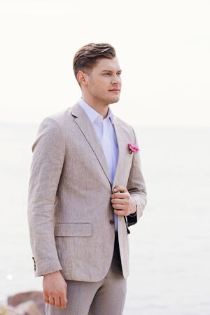dreamy bridegroom in formal wear with pink boutonniere looking away
