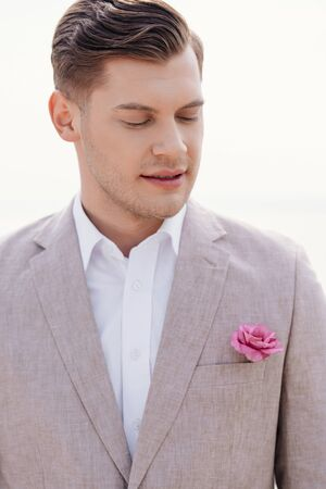 pensive bridegroom in formal wear with boutonniere with closed eyes
