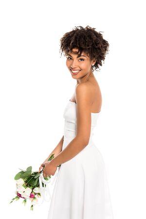 mariée afro-américaine bouclée tenant le bouquet et regardant la caméra isolée sur blanc